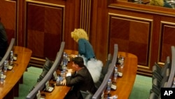 Smoke rises after Kosovo opposition lawmaker Donika Kada Bujupi ignites a tear-gas canister, disrupting Parliament's session for the third time in row, Pristina, Oct. 23, 2015.