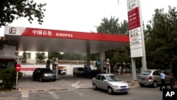 FILE - Motorists pump fuel at a Sinopec gas station in Beijing, China, Aug. 29, 2011.