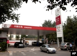 FILE - Motorist pump fuel at a Sinopec gas station in Beijing, China, Aug. 29, 2011.
