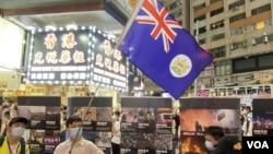 反送中運動6-12一周年十八區街頭展覽,在銅鑼灣展覽場地有人高舉港英殖民時代香港旗幟。