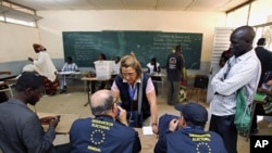 Observers from the European Union watch Senegalese electoral officials count ballots during presidential elections in the capital Dakar, February 26, 2012