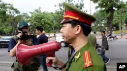 FILE - A Vietnamese police officer uses a speaker to order pedestrians including journalists to leave a closed area near the Chinese Embassy in Hanoi, Vietnam.