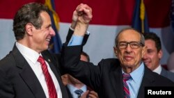 FILE - Former New York Governor Mario Cuomo celebrates with his son, Andrew, after the younger Cuomo won re-election as governor of the state, Nov. 4, 2014.