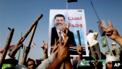 Supporters of Egypt's Islamist President Mohammed Morsi flash victory signs during a rally, Nasser City, Cairo, July 3, 2013.