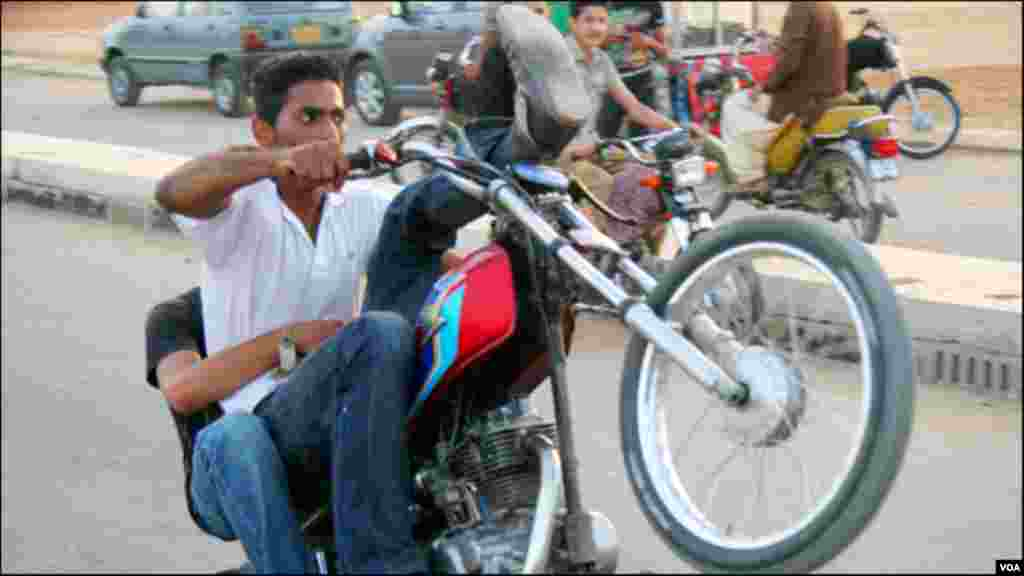 ایک پہئے پر موٹر سائیکل چلانے کا مظاہرہ کرتا ہوا نوجوان