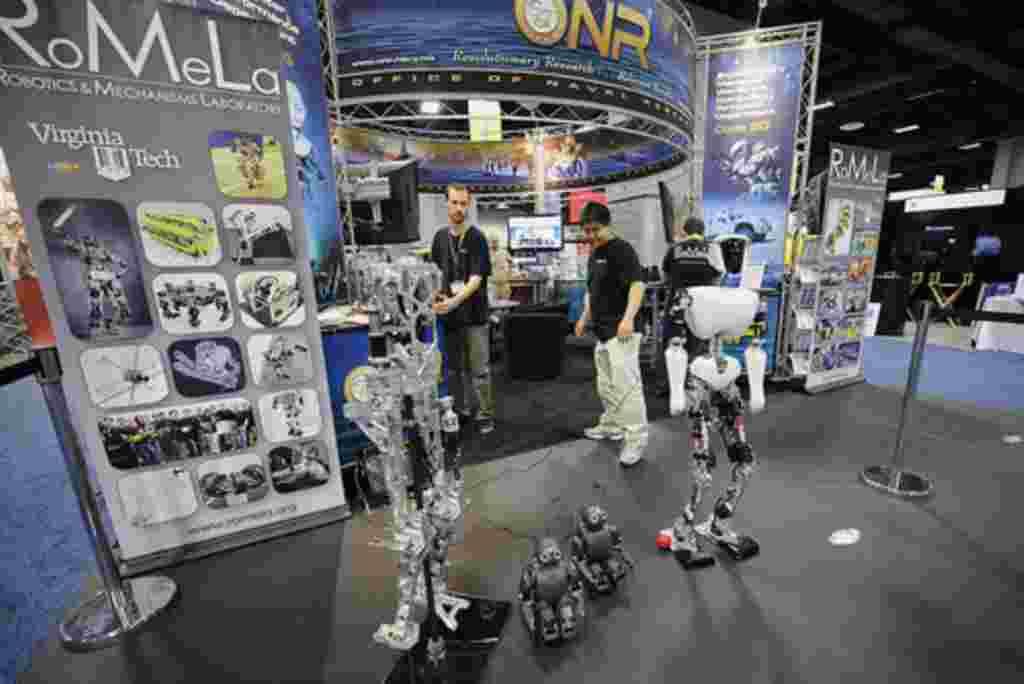 Michael Hopkins, a la izquierda, y Bryce Lee, estudiantes de posgrado en el Tecnológico de Virginia, trabajan en el Laboratorio de Robótica y Mecanismos en una demostracón de robots autónomos, en la Oficina de Investigación Naval de la exposición durante