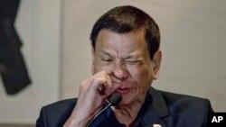 Presiden Filipina Rodrigo Duterte mendemonstrasikan bagaimana pecandu narkoba mengirup zat tersebut dalam konferensi pers di Beijing, Oktober 2016. (AP/Ng Han Guan)