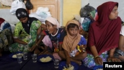 Migrants believed to be Rohingya take their breakfast inside a shelter after being rescued from boats at Lhoksukon, in Indonesia's Aceh Province, May 12, 2015.