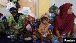 Migran yang diyakini berasal dari Rohingya mendapat sarapan setelah diselamatkan dari kapal di Lhoksukon, Aceh, Selasa (12/5).me