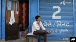 A man speaks on a mobile phone in front of shop displaying an advertisement for Uninor in Mumbai, India, February 6, 2012. Norway's Telenor plans to fight an order by India's Supreme Court to cancel 22 telecoms licences held by its Indian joint venture, b