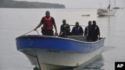 Una lancha de la policía marina de Jamaica regresa a Puerto Antonio luego de buscar los restos de la avioneta siniestrada.