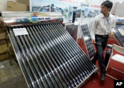 FILE - A solar water heater, left, and a solar panel, right, are seen at Entech Hanoi, an international trade fair on energy efficiency and the environment, at the Giang Vo Exhibition Center in Hanoi, Vietnam.