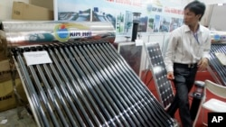 FILE - A solar water heater, left, and a solar panel are seen at Entech Hanoi, an international trade fair on energy efficiency and the environment, at the Giang Vo Exhibition Center in Hanoi, Vietnam.