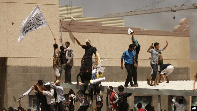 "A Yemeni protestor, left, holds a white flag that reads, ""No God but Allah, and Mohammed is his prophet,"" in front of the U.S. Embassy during a protest in Sanaa, Yemen, Sept. 13, 2012."