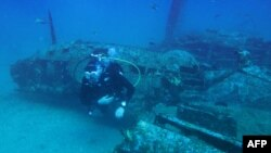 A diver explores the wreckage of an American bombardier fighter plane from the Second World War, the Lockheed P-38G Lightning, at 38 meters of depth, on August 12, 2018, off the coast of La Ciotat, southern France.