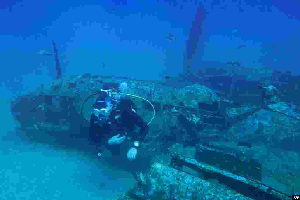A diver explores the wreckage of an American bombardier fighter plane from the Second World War, the Lockheed P-38G Lightning, at 38 meters of depth, off the coast of La Ciotat, southern France.
