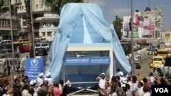 Palestinos aplauden en la ceremonia del sillón gigante. Por su parte, EE.UU. ha dicho que utilizará su veto, para evitar el voto.
