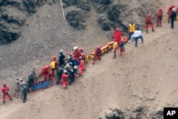 In this photo provided by the government news agency Andina, rescue workers surround an injured man on a stretcher who was lifted up from the site of a bus crash at the bottom of a cliff, in Pasamayo, Peru, Jan. 8, 2018.