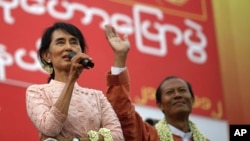 Burma's pro-democracy leader Aung San Suu Kyi (L) gives her speech beside the National League for Democracy party's candidate for the Seikkan Township constituency, Dr. Myo Aung at Seikkan, Rangoon, March 21, 2012