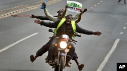 FILE - A motorcycle carrying protesters holding a placard using the acronym of the national electoral commission, drives ahead of demonstrators on foot calling for the disbandment of the commission over allegations of bias and corruption, in Nairobi, Kenya, June 6, 2016.