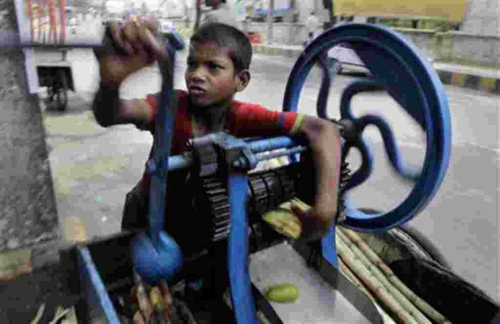 Munna, de 11 años, obtiene extractos de jugo de caña de azúcar en Gauhati, India.