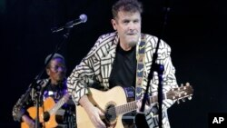 FILE - In this Nov. 6, 2010 file photo, South African musician Johnny Clegg performs during a concert in Johannesburg. Clegg blended Western pop and Zulu rhythms in multi-racial bands during white minority rule.