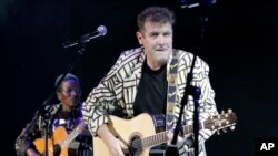 FILE - In this Nov. 6, 2010 file photo, South African musician Johnny Clegg performs during a concert in Johannesburg.