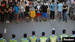Barisan polisi berhadapan dengan para demonstran pro-Demokrasi dekat gedung pemerintah pusat di Hong Kong (13/10).