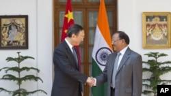 印度国家安全顾问多瓦尔(右)和中国国务委员杨洁篪2015年3月23日(星期一)在新德里举行的第18轮印中边界争议会谈前握手。
