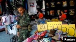Thailand's junta kept many of the thousands of troops and police off the streets as the number of people making a public show of dissent to the May 22 coup dwindled. A soldier stand guards at a shop at Chatuchak market in Bangkok, Thailand, June 8, 2014.