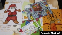 """Envelopes addressed to """"Pere Noel"""" - Father Christmas in French - decorated with love hearts, stickers and glitter, are displayed by postal workers in Libourne, southwest France, Monday, Nov. 23, 2020. (AP Photo/Francois Mori)"""