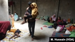 A sick Rohingya refugee is carried from one room to another in a Rohingya refugee camp in West Bengal, eastern India in April 2018. After receiving threats from the Hindu nationalists group in north India, where they lived for years since fleeing Myanmar, the refugees fled to eastern India in March.