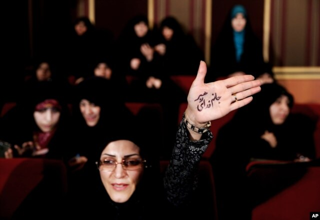 "An Iranian raises her palm bearing Persian that reads, ""I'm ready to sacrifice myself for the supreme leader,"" in Tehran, Feb. 24, 2016. During election campaigns and to humiliate reformists, hard-liners have accused their reformist rivals of being backed by the British government."