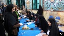 Peserta pemilu Iran (kiri) tiba di TPS untuk mengikuti pemungutan suara parlemen di Teheran, Iran (26/2).