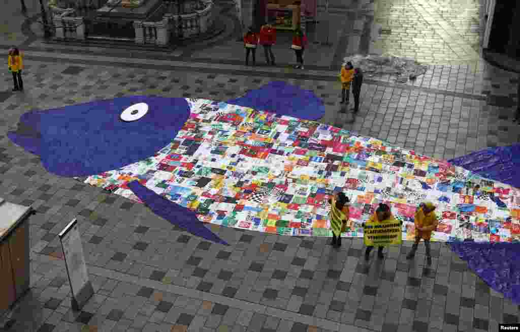 About 800 shopping bags made of plastic sewed together in the shape of a fish are laid out by environmental activist group Greenpeace during a protest against the pollution of oceans by plastic, in a street in Vienna, Austria.