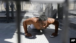 Condemned inmate Donald DeBose does pushups in a caged recreation yard space of the adjustment center on death row at San Quentin State Prison in San Quentin, Calif., Aug. 16, 2016. A pair of November ballot measures will decide the future of the death penalty in California.