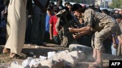 Un présumé combattant du groupe Etat islamique détruit des objets anciens et un site du patrimoine mondial de l'Unesco situé au nord-est de Damas, dans la ville de Manbij, au nord-est d'Alep (transmise par la propagande islamiste média Welayat Halab à l'AFP, 2 juillet 2015).