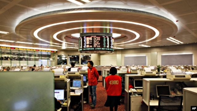 Floor traders walk inside the trading hall of the Hong Kong Stock Exchange, March 2, 2011