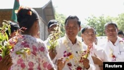 A woman presents flowers to former Myanmar ruling Union Solidarity and Development Party (USDP) chief Shwe Mann, as he campaigns at a village near his hometown Kanyuntkwin, Myanmar, Nov. 4, 2015. Myanmar will hold its historic general election on November