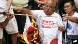 Anti-Japan protesters burn Japanese flags outside the Japanese Consulate General in Hong Kong, September 16, 2012.