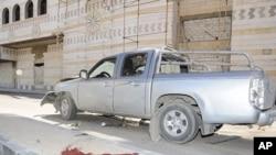 Máu loang trên vỉa hè cạnh chiếc xe bị hư sau vụ tấn công bằng xe cài bom ở Damascus, hôm 24/4/2012 (Hình do hãng thống tấn SANA của Syria công bố)
