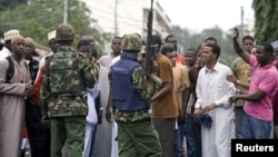 Kenyan policemen watch over youths protesting against the killing of Sheikh Aboud Rogo Mohammed, Mombasa, August 31, 2012.