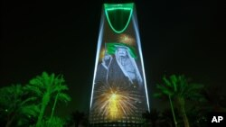 FILE - In this photo taken Sept. 24, 2017, and released by the Saudi Culture and Information Ministry, an image of King Salman and Crown Prince Mohammed bin Salman are projected on the Kingdom Tower in Riyadh, Saudi Arabia. A court in Saudi Arabia sentenced a columnist to five years in prison for insulting the Saudi royals.
