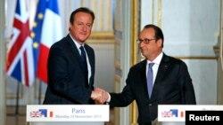 英国首相卡梅伦(左)在联合记者会上和法国总统奥朗德握手(2015年11月23日)