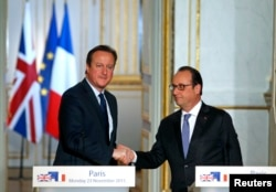 French President Francois Hollande (R) shakes hands with Britain's Prime Minister David Cameron during a joint news conference, Nov. 23, 2015.