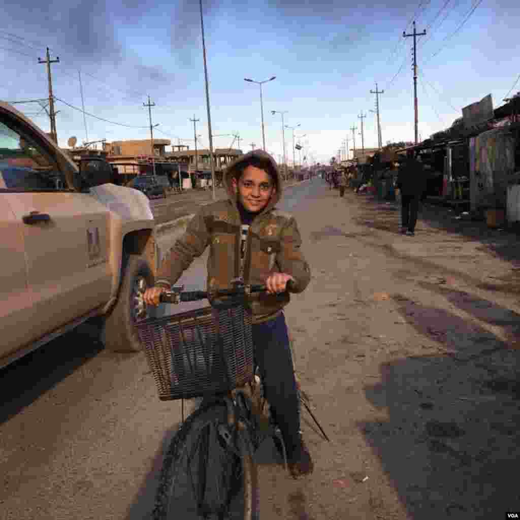 A boy rides his bike to the local market in Qayyarah town, south of Mosul, December 2016. (Kawa Omar/VOA)