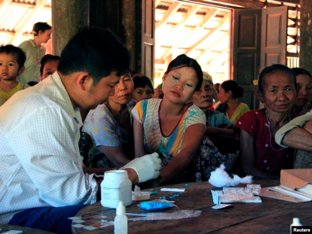 FILE - A government health worker takes a blood sample from a woman to be tested for malaria in Ta Gay Laung village hall in Hpa-An district in Kayin state, southeastern Myanmar, Nov. 28, 2014.