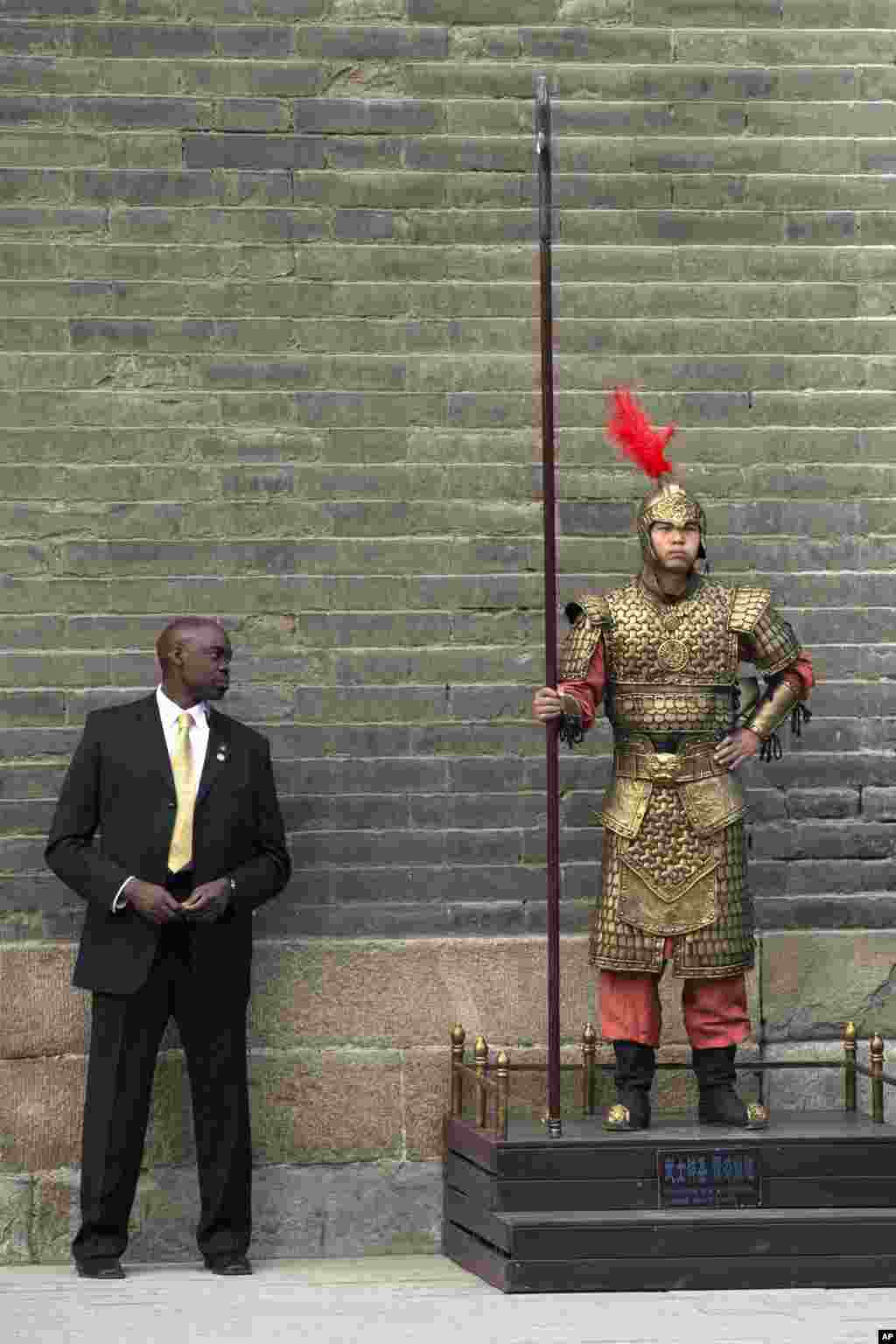 A U.S. secret service officer checks a Chinese performer dressed as an ancient warrior as U.S. first lady Michelle Obama visits a nearby city wall in Xi'an, in northwestern China's Shaanxi province.