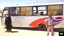Seorang polisi dan pendeta Kristen Koptik berada di lokasi pasca serangan atas sebuah bus penumpang di Minya, Mesir hari Jumat (26/5).