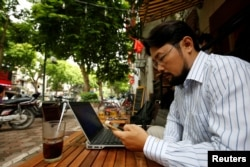 FILE - Vietnamese activist Anh Chi searches the internet at Tu Do (Freedom) cafe in Hanoi, Vietnam August 25, 2017.
